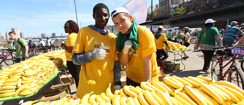 Two TD Bike Tour volunteers hand out bananas