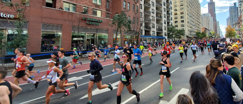 Multiple marathon runners on a city street, buildings in the background