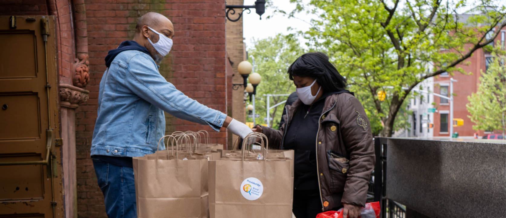 Male volunteer wearing a face-mask standing outside a church handing a food bag to a woman.