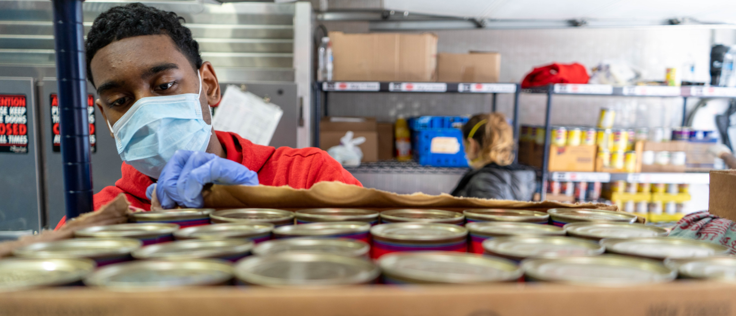 Male volunteer, in a red shirt, stocking cans of salmon at food pantry.