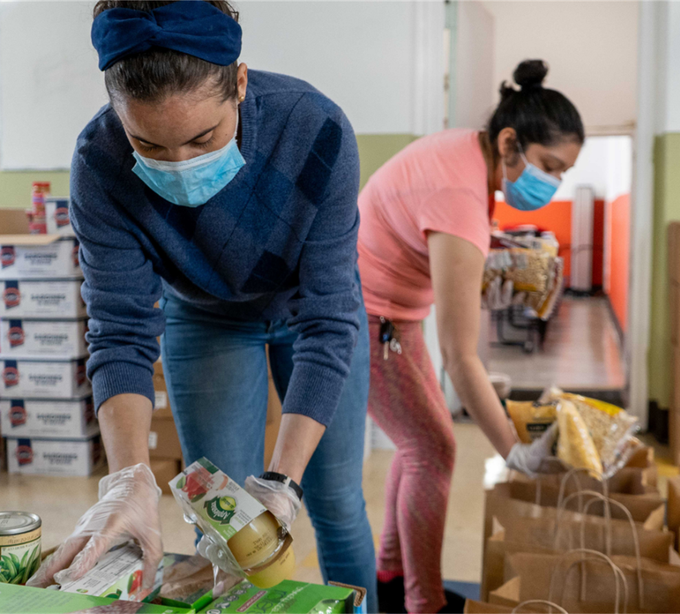 Two female volunteer packing food'