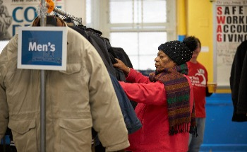 Woman looking for a coat at a 2018 Coat Drive event.