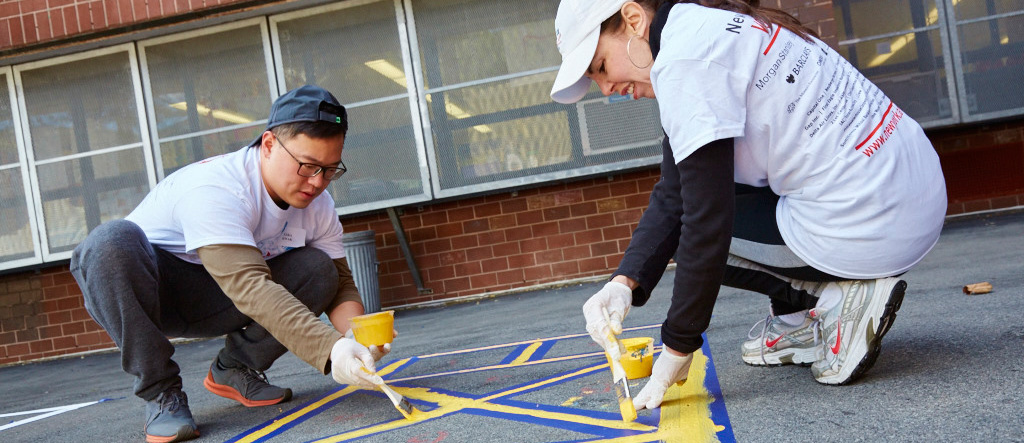 New York Cares Day Fall Volunteering in Schools Man and Woman Paint Schoolyard