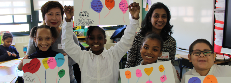 New York Cares volunteers working with school children creating Valentines Day cards