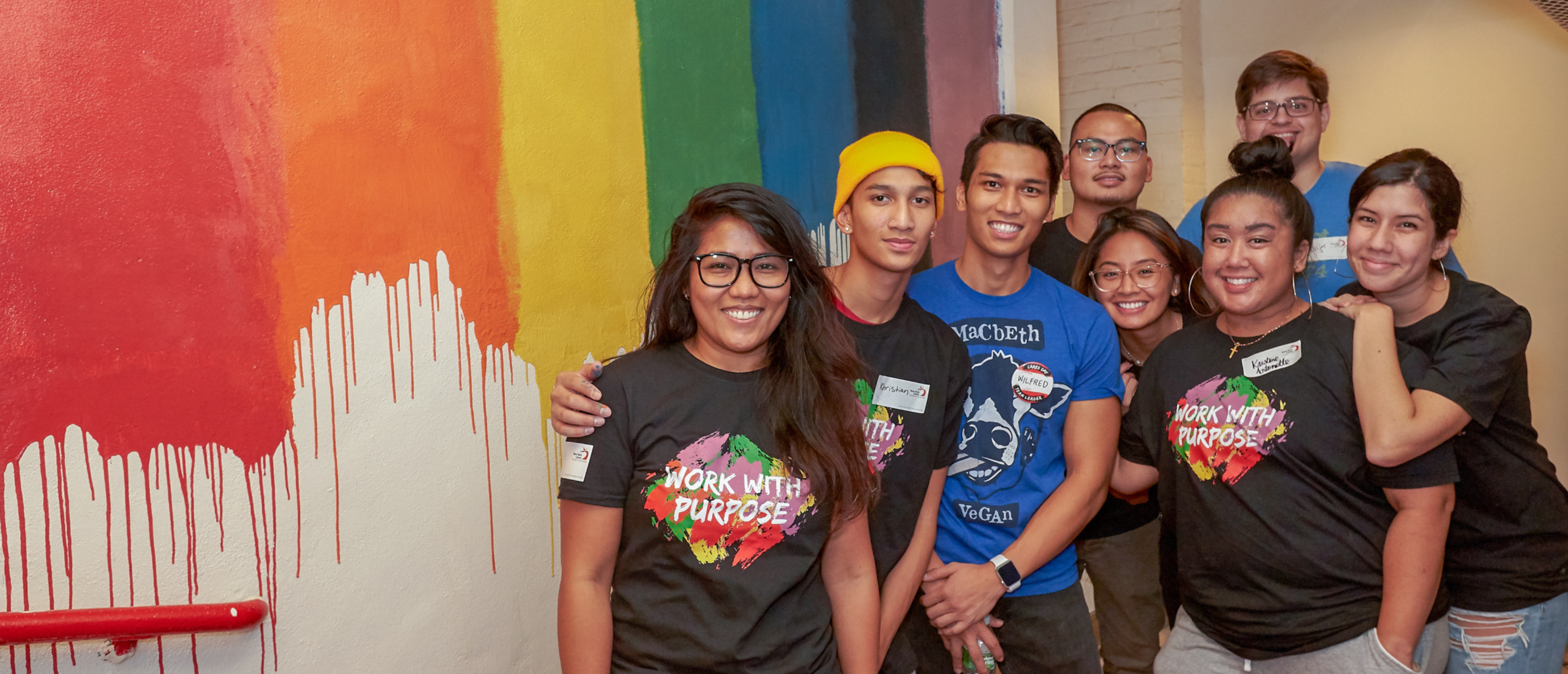 Group of volunteers in front of colorful mural