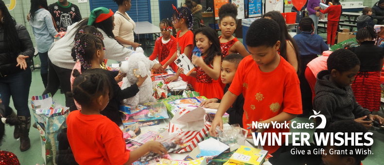 Child receiving a New York Cares Winter Wishes package