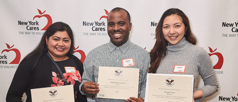Three volunteers holding up their Presidential Service Award certificates, in front of a New York Cares branded press wall.