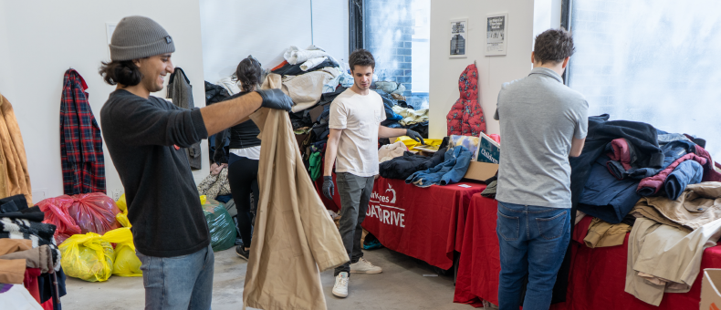 Three young volunteers sorting through donated winter coats for the New York Cares Coat Drive.