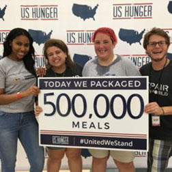 Volunteers pose after making 500,000 meals to donate to those in need.