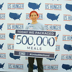 Kathy Wang, Table Captain, proudly holds up a sign displaying the packing of 500,000 meals.