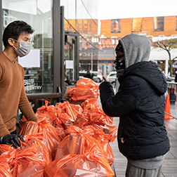Volunteer distributing food at the Barclays Center in Brooklyn, NY
