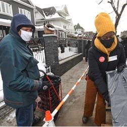 New York Cares Volunteer handing out a coat to a Queens resident.