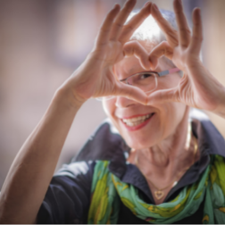 Older female creating a heart with her hands