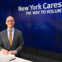 Executive Director, Gary Bagley posing by the New York Cares logo on a blue background