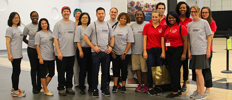 New York Cares volunteers pose before packing 500,000 meals.