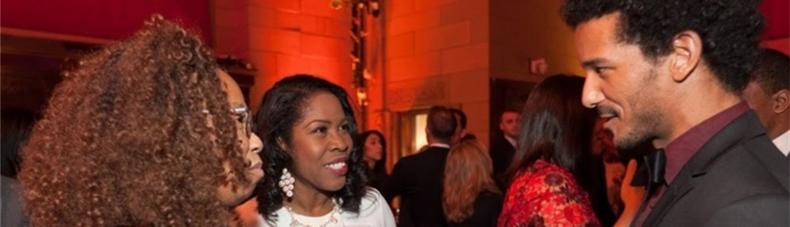 Two females having a conversation with a male at the New York Cares Gala