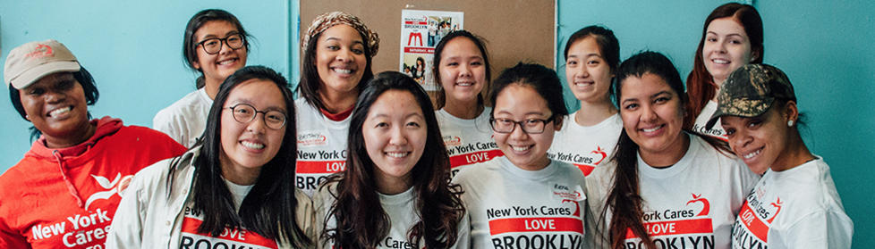 Volunteers smiling after painting Brooklyn Democracy Academy.