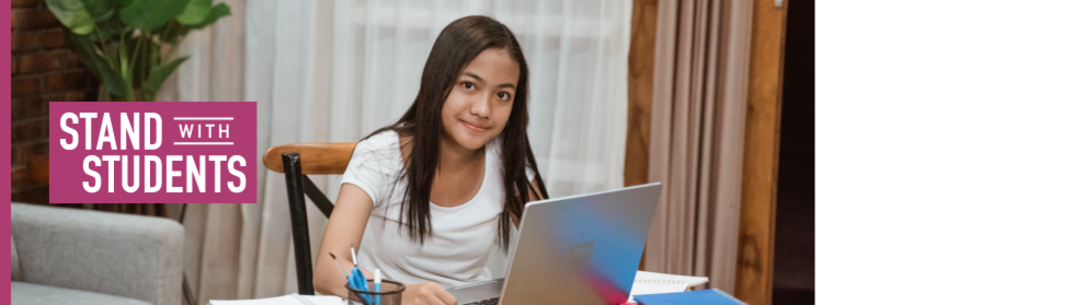 Young girl sitting behind her desk at home doing homework, looking at the camera with the Stand with Students logo on the left side.